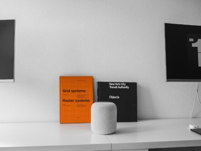 White desk with orange and black books leaning on wall