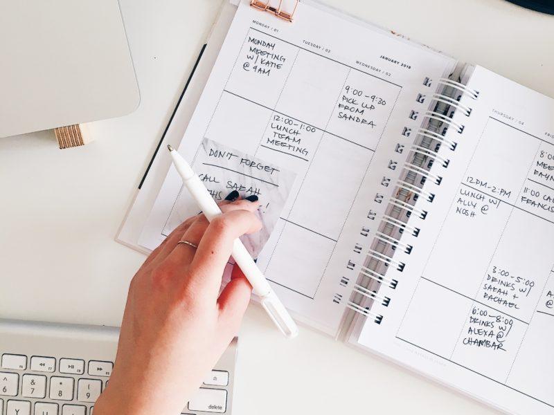 Hand on planner at desk